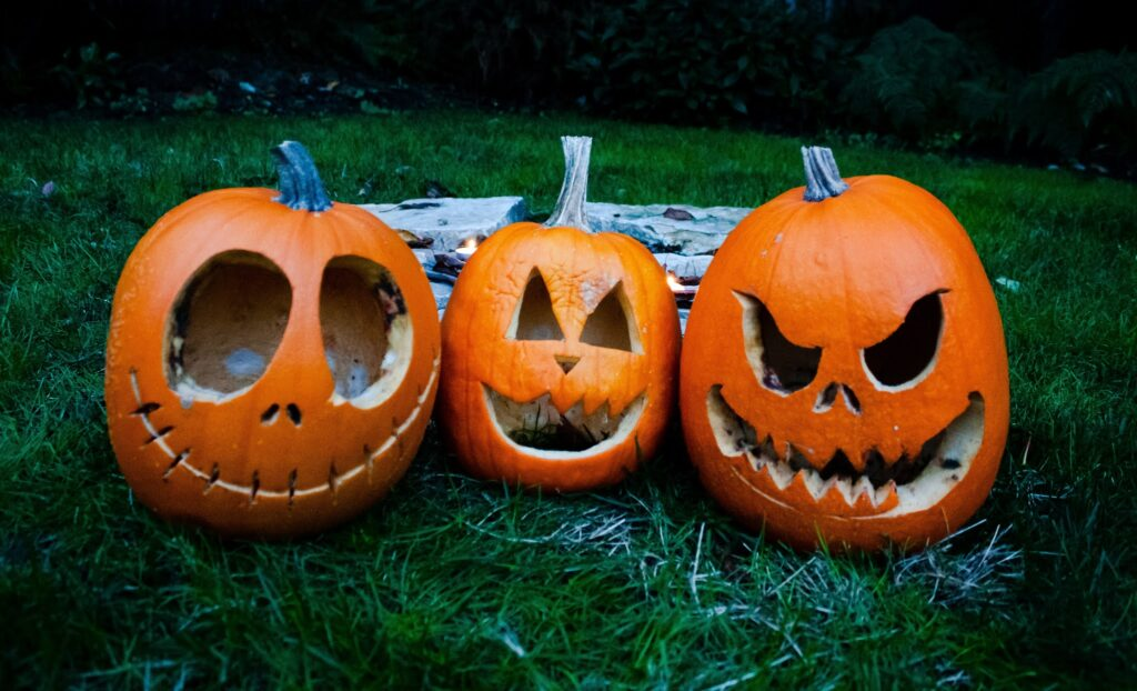 three scary Halloween pumpkins try to scare you