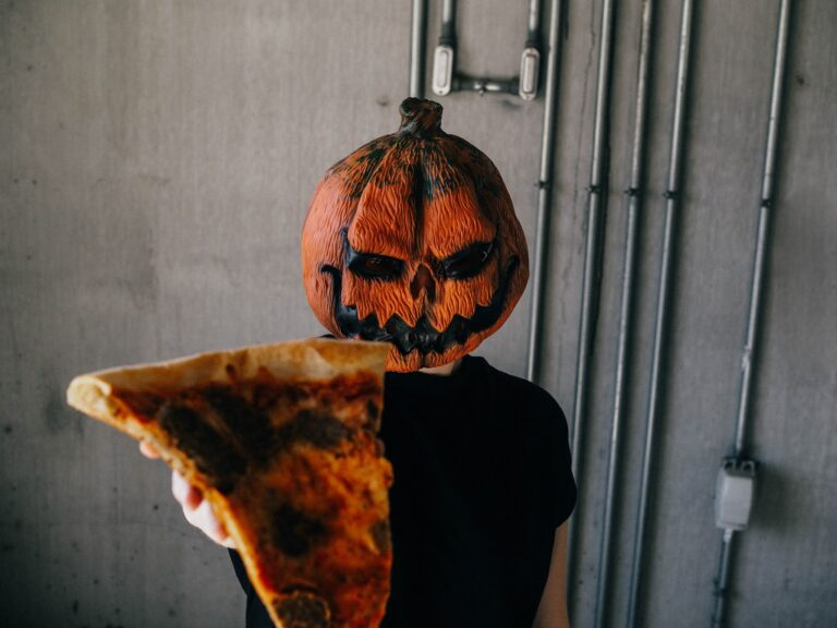 Happy Halloween Image with scary man offering pizza slice with pumpkin mask