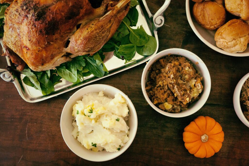 In this frame lot of foods just like roasted duck, pumpkin and slices of bread